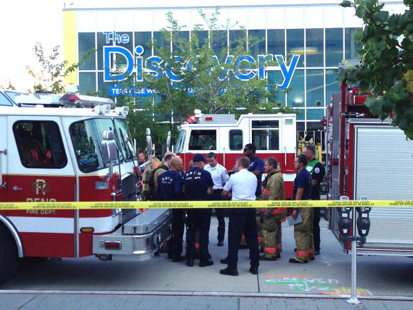 Image: Firefighters confer out side the Nevada Discovery Museum in Reno, Nev.