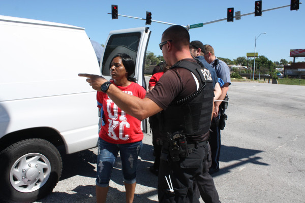 Image: Police in Kansas City handcuffed Latoya Caldwell, 31, and led her into a police van after she was arrested with dozens of other fast food workers who participated in civil disobedience. Caldwell arranged for a friend to pick up her four children fr