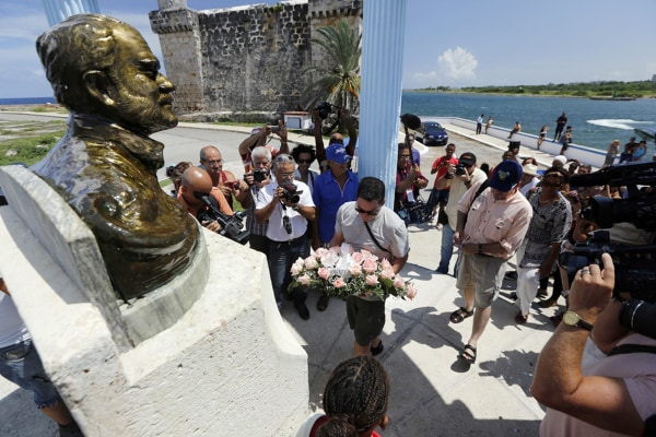 Image: The grandsons of Ernest Hemingway, John and Patrick, and others lay a wreath at the bust of the acclaimed writer
