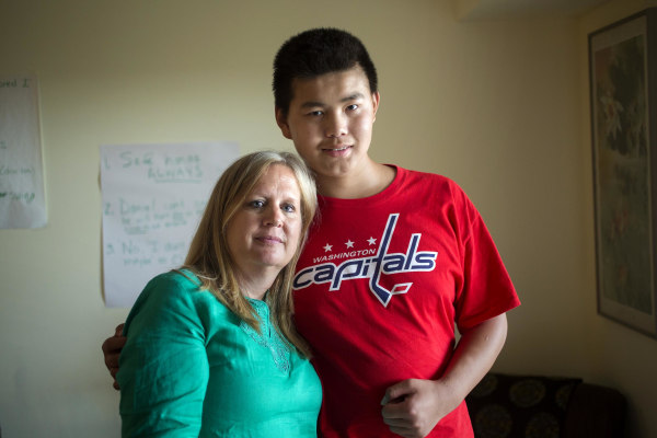 Image: Christine Ogden converses using sign language with her adopted son Daniel