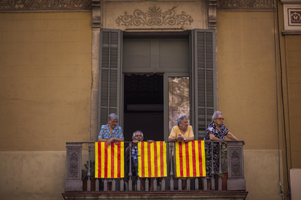 Image: People stand on a balcony decorated with Catalonia flags in Barcelona