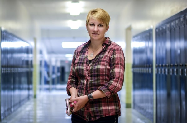 IMAGE: Kasey Hansen poses with her handgun in the hallway outside one of her classrooms at Valley Junior High School
