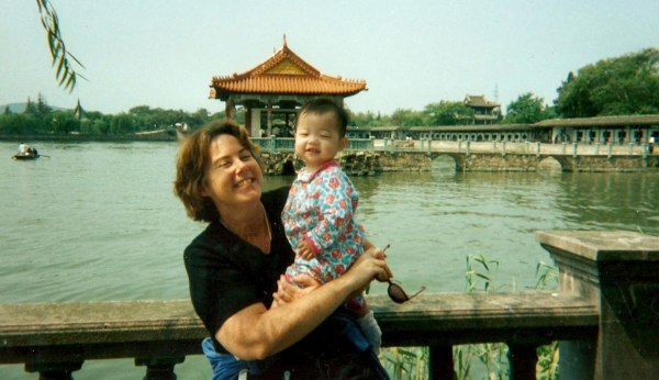 Image: Kate Crotty poses with mom in Wuxi, China during adoption process in 1997.