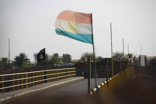 "Image: A Kurdish and an ISIS flag on a bridge at the village of ""Mula Abdula"" in Kirkuk, Iraq"