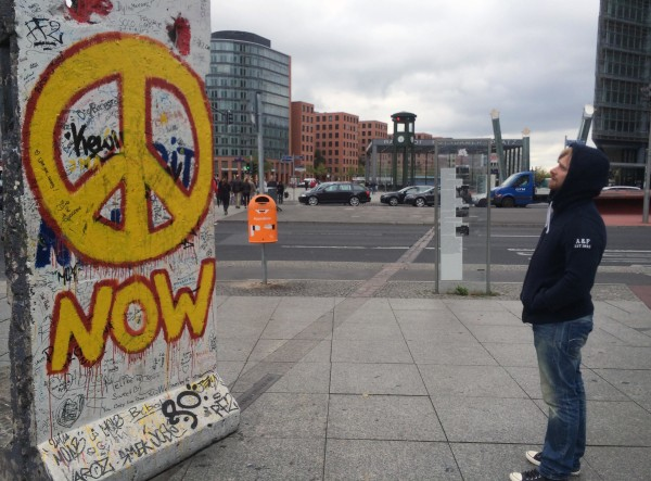 Image: A young man looking at a slab of the former Berlin Wall at Potsdamer Platz