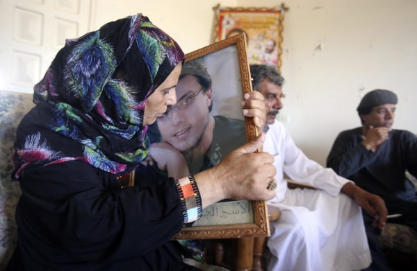 Image: Ahmad Asfour's mother kisses his picture at her house in Khan Younis in the southern Gaza Strip
