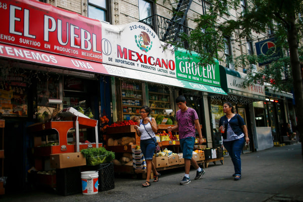 Image: People pass by a Mexican grocery store in Harlem, N.Y., on Aug. 10.