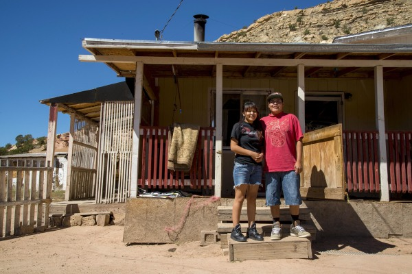 Image: The home of Tammy Lee sits below the mesa where she has lived her entire life. Her spouse Levi takes a picture with her on their front porch.