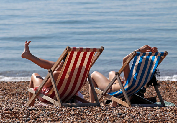 Image: People enjoy the sunshine on a beach.