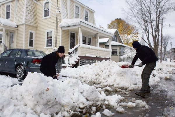 Image: Candice and Andre Schoth shovel away a snow pile from plowing at the end of their driveway on Dean Street in Bangor