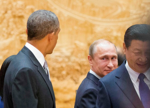 Image: Putin looks back at Obama as they arrive with Xi Jinping at APEC Summit plenary session in Beijing