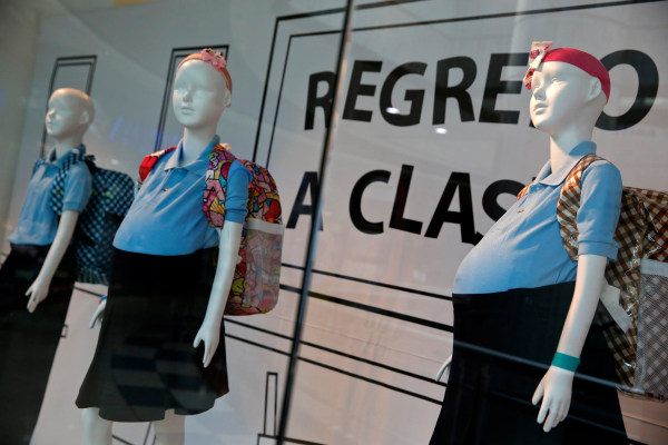 Image: Mannequins of pregnant schoolgirls are seen in a shop window at a shopping mall in Caracas