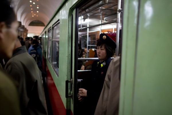 A conductor stands inside a train at Puh