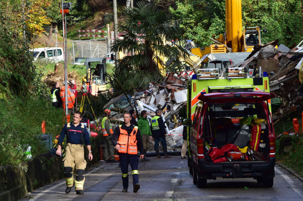 Image: Rescuers work near the rubbles of a small apartment building after it was destroyed by a landslide