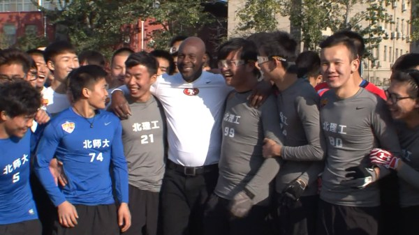 Jerry Rice poses with aspiring football players after a practice session in Beijing.