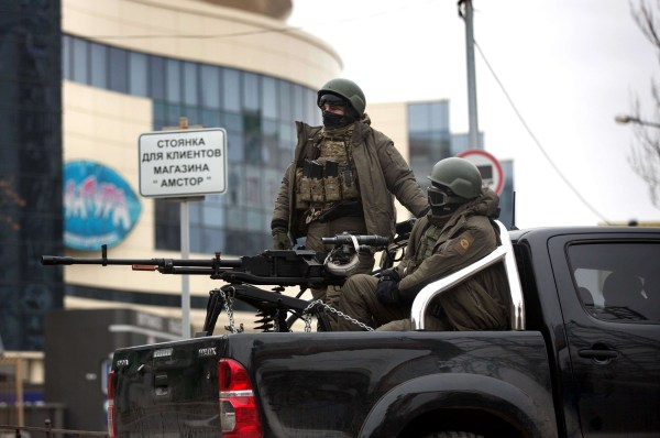 Image: Pro-Russian gunmen sit in the back of a vehicle mounted with a machine gun in the center of the eastern Ukrainian city of Donetsk