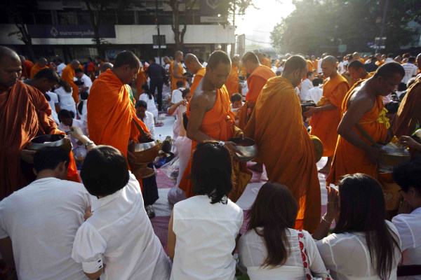 Image: Buddhist monks walk past people to collect donations from them during a mass alms-offering ceremony in Bangkok's shopping district