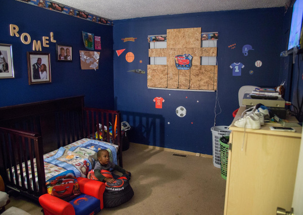 Image: Two-year-old Romel Howard watches TV in bedroom of his family's  Hillsdale, Missouri home.