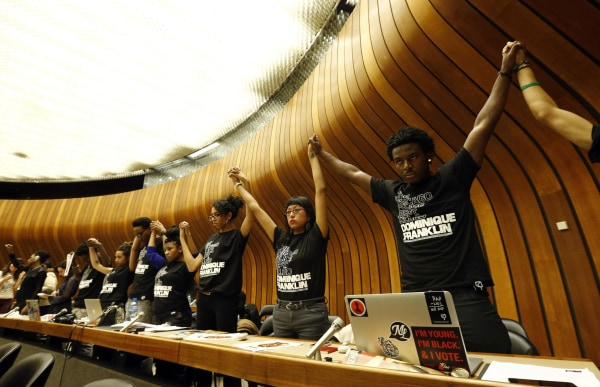 Image: Activists hold hands during a silent protest at a hearing of the United States at the Committee against Torture at the United Nations in Geneva
