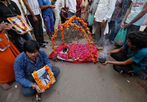 Image: A boy holds a photograph of Sonu, a female stray dog, as others prepare to bury the dog in Ahmedabad