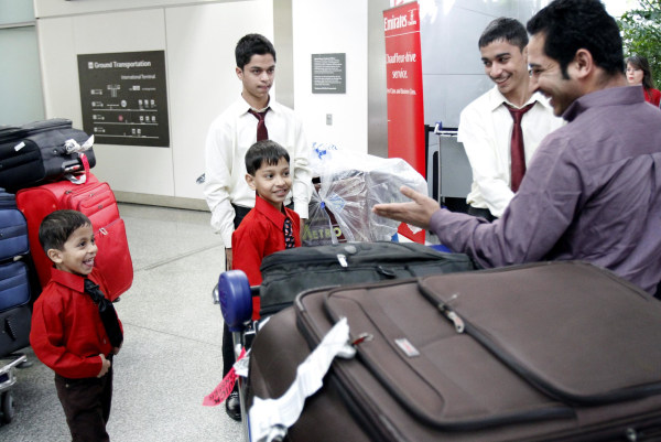 Image: Mohammad Usafi, right, greets his brothers as they come out of customs at San Francisco International Airport