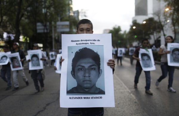Image: A demonstrator carries a photograph of Mora Venancio, one of the 43 missing trainee teachers, during a march in support of the students in Mexico City