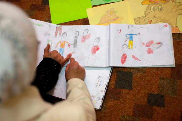 Image: Aya points at drawings, depicting violent scenes, she made recently, about life in Aleppo, Syria.