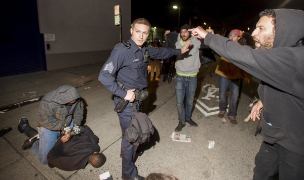 Image: Police officer holds back anti-police demonstrators as an undercover officer makes an arrest in Oakland