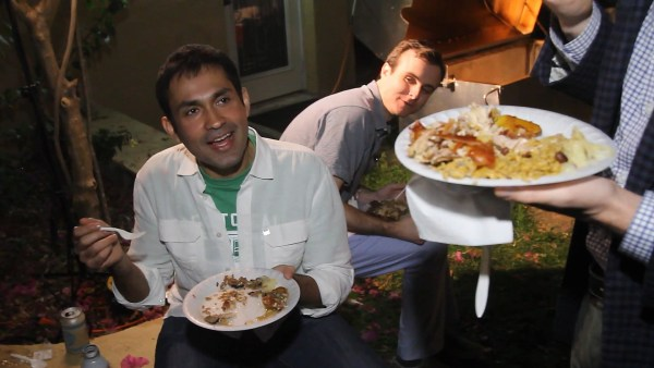 Image: A party-goer enjoys the slow-roasted pork.