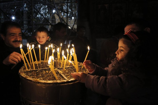 Image: Visitors light candles in the Church of the Nativity, the site revered by Christians as Jesus' birthplace, ahead of Christmas in Bethlehem,  West Bank