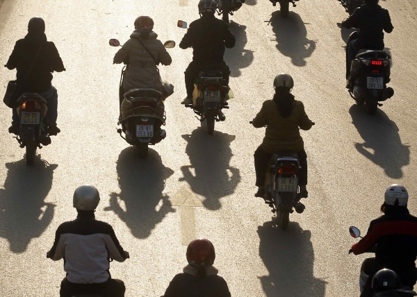 Image: Motorcyclists ride on a street in Hanoi