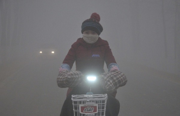 Image: A woman rides her electric bicycle along a street amid thick haze in Chiping county