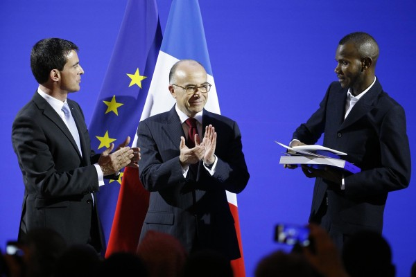 Image: French Prime Minister Valls and Interior Minister Cazeneuve applaud as Lassana Bathily, 24, holds his citizenship papers during a ceremony at the Interior Ministry in Paris