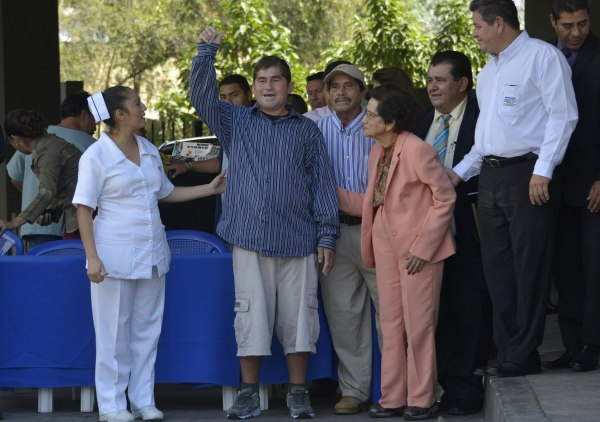 Image: Castaway fisherman Alvarenga  waves next to a nurse and El Salvador's Health Minister Rodriguez while leaving the hospital in Santa Tecla