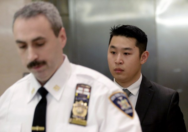 Image: New York City Police (NYPD) officer Peter Liang (R) is escorted by a court officer inside the criminal court after an arraignment hearing in the Brooklyn borough of New York City