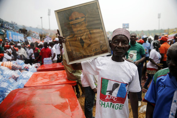 Image: A supporter holds a framed portrait of Muhammadu Buhari