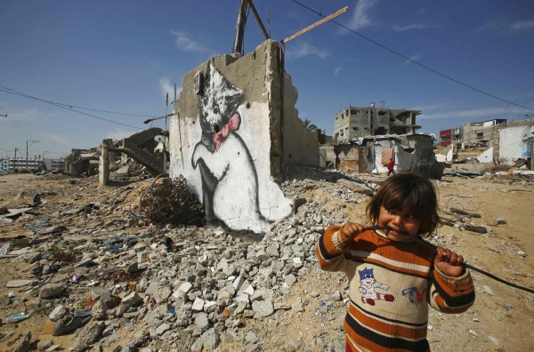 Image: Palestinian girl looks on as a mural of a playful-looking kitten, presumably painted by British street artist Banksy, is seen on the remains of a house wall, in Biet Hano