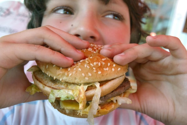Photo: A boy eats a hamburger.