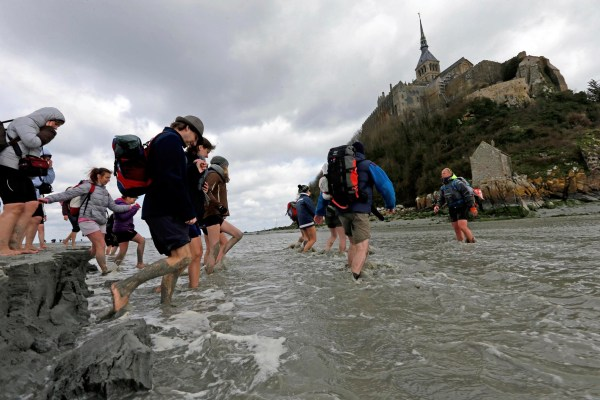 Image: Sebastien Daligault, a guide at the Bay Saint-Michel, stands knee-deep in water during a walking tour around the Mont Saint-Michel off France's Normandy coast