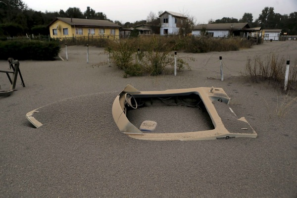 Image: A boat is seen in a house backyard at Ensenada town which is covered with ash from Calbuco volcano