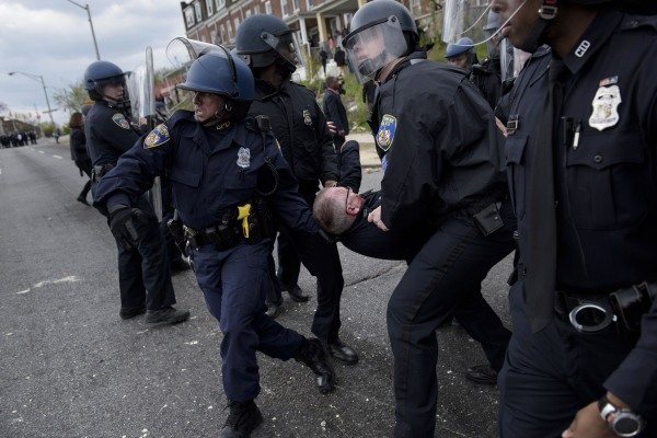 Image: Baltimore police officers carry an injured comrade
