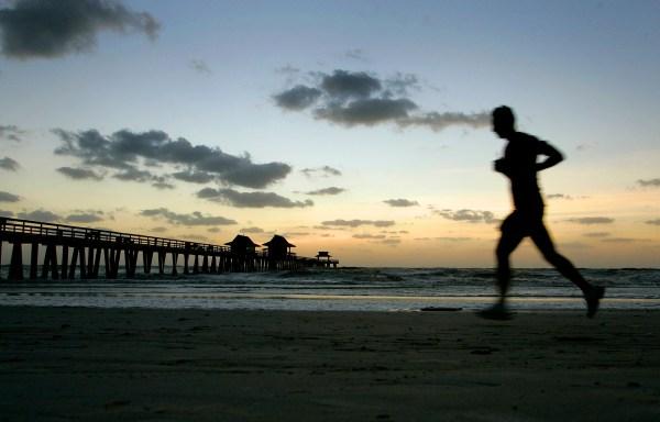 Image: A man runs along the beach near Naples Pier