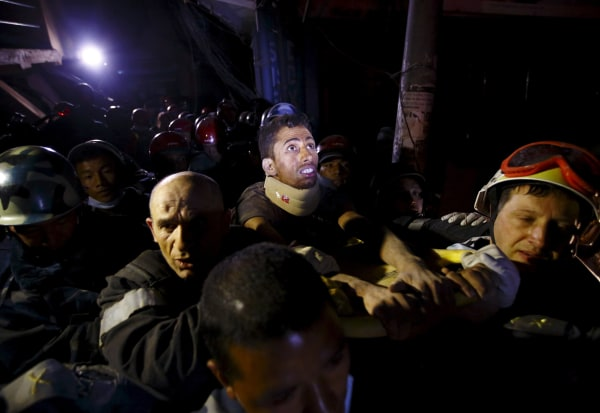 Image: Injured survivor Rishi Khanal looks around at the surroundings as he is rescued by Armed Police Force and the French rescue team, after being trapped for four days in a collapsed building following Saturday's earthquake, in Kathmundu