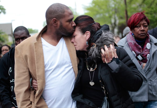 Image: Jeff Jackson, left, comforts his girlfriend, Andrea Irwin, the mother of Tony Robinson