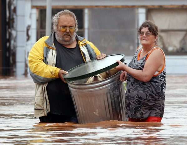 Image: George and Susan Kruger make one of three trips with their animals from their flooded house to safety on Sunday, May 24, 2015 in Purcell, Okla.