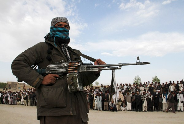 Image: A member of the Taliban and onlookers during the execution of three men in Afghanistan's Ghazni province