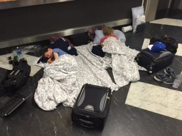 Image: Evan (L) and Erick Sliter, aged 8 and 10, sleeping on the floor of Belfast International Airport, Northern Ireland, early Sunday.