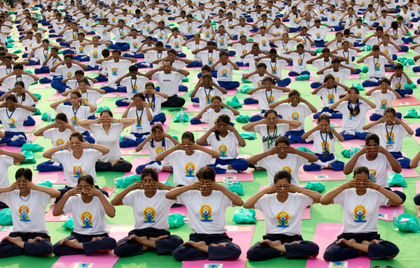 Image: Indians perform yoga on Rajpath, in New Delhi