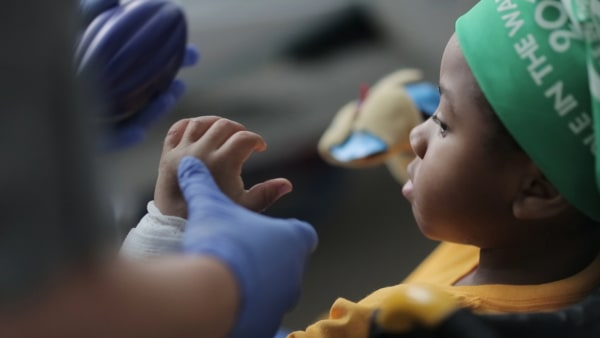 Image: Zion Harvey, 8, looks at his new hand after receiving a bilateral hand transplant earlier this month.
