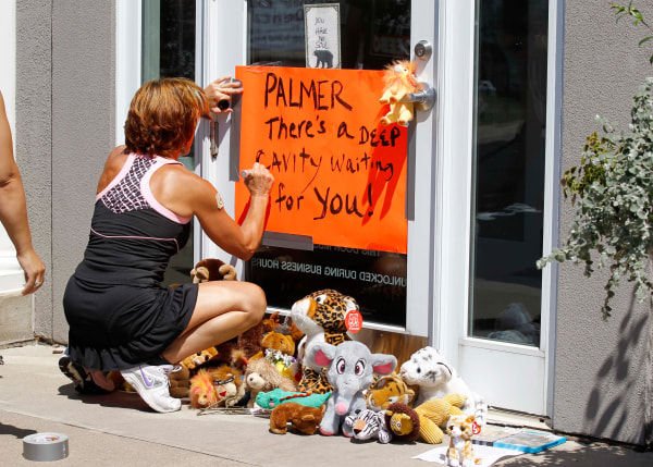 Image: A woman writes on a sign outside Dr. Walter James Palmer's dental office